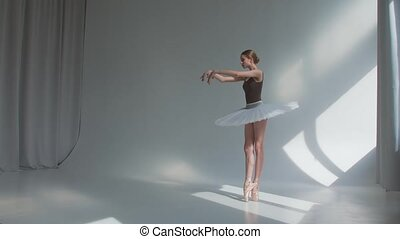 Female dancer does ballet exercises in stage dress with open...