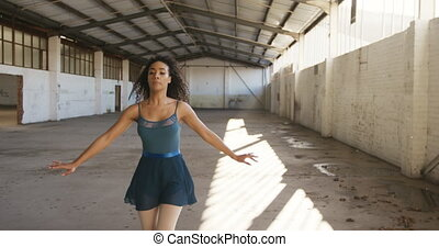 Female dancer in an empty warehouse - Front view of a mixed ...