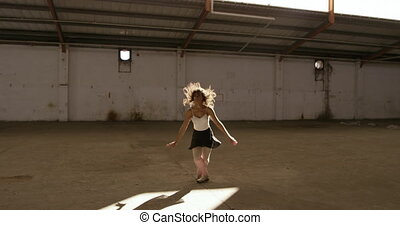 Front view of a mixed race female ballet dancer practicing in an empty warehouse, dancing and jumping, slow motion. Cool Generation Z hipster style concept.