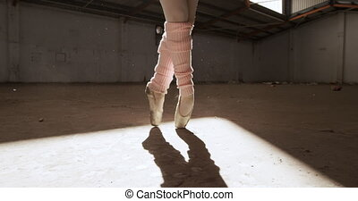 Front view of legs of a female ballet dancer practicing in an empty warehouse, standing on tiptoes, slow motion. Cool Generation Z hipster style concept.