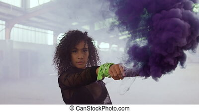 Portrait of mixed race female in an empty warehouse, looking to camera and holding smoke grenade, slow motion. Cool Generation Z hipster style concept.