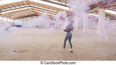 Side view of mixed race female dancer in an empty warehouse, running and holding smoke grenade, slow motion. Cool Generation Z hipster style concept.