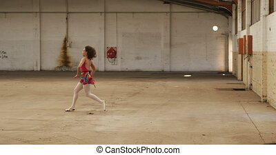 Female dancer in an empty warehouse - Side view of a mixed ...