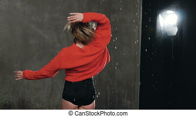 Female dancer in red sweater dancing under the drops of water in the studio before studio light, . Rain, sexy girl dancer in black shorts and red sweater makes circles around herself. Dancing girl