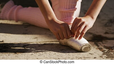 Female dancer puts on her ballet shoes on a rooftop - Front ...