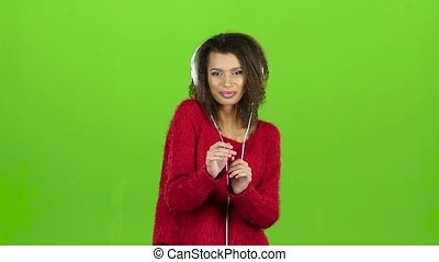 Female dances and smiles with headphones, green screen. Slow...