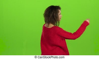 Female dancing back to viewer on green screen, slow motion