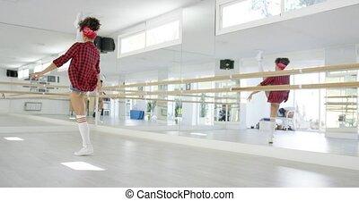 Female dancing student takes steps in studio