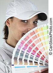 Female decorator choosing color from swatch