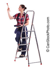Female decorator climbing a ladder