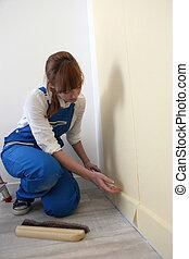Female decorator hanging wallpaper