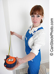 Female decorator measuring a wall