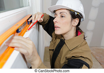 female decorator measuring wall