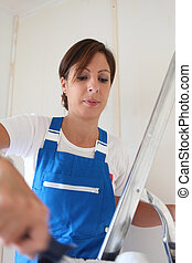 Female decorator painting a room white