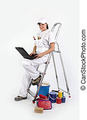 Female decorator perched on ladder to use laptop