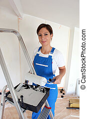Female decorator stood on step-ladder