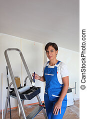 Female decorator with stepladder