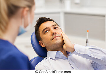 female dentist and male patient with toothache - people,...