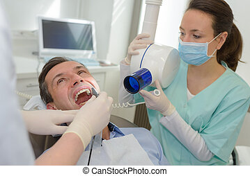female dentist checking male patients teeth
