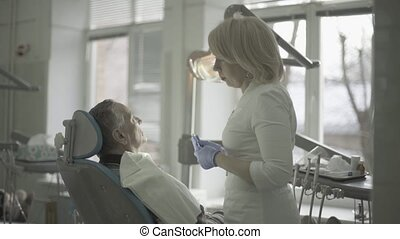 Female dentist communicates with a client 4k