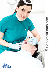 Female dentist examines a patient