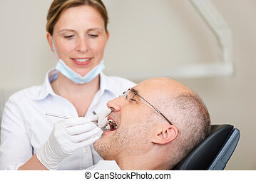 Female Dentist Examining Male Patients Mouth