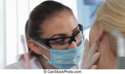 Female dentist finishes checkup of the patient