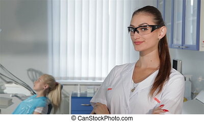Female dentist gestures okay at the dental clinic -...