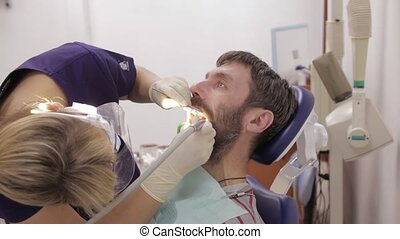 female dentist is treating a patient in dental clinic. Dental check up. Stomatologist treats caries in patient's teeth