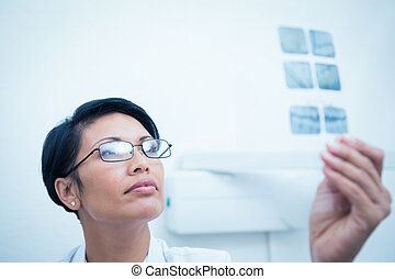 Female dentist looking at x-ray