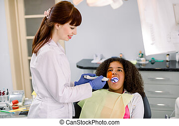 Female dentist performing dental filling procedure to a little mixed raced school girl in pediatric dental clinic. Doctor using dental ultraviolet curing light for filling polymerization