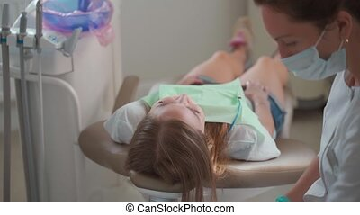 Female dentist preparing for checking up patient teeth with ...