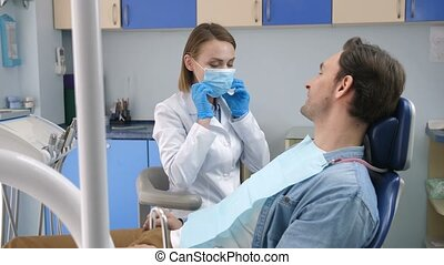 Female dentist starting check-up on male client - Pretty...