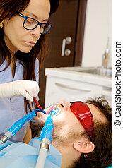 Female dentist whitening teeth of male patient