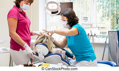 Female dentist with assistant treating patient sitting in dentist chair