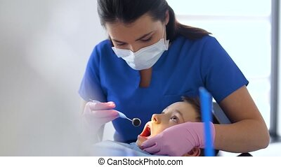 female dentist with kid patient at dental clinic - medicine,...