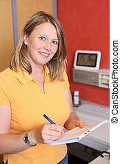 Portrait of confident female dentist writing on document at desk in clinic