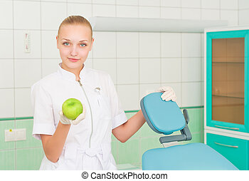 female dentists shows green apple