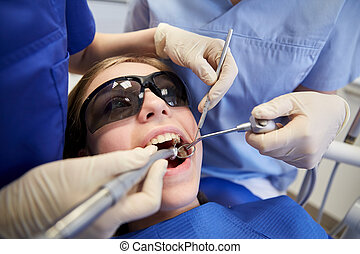 female dentists treating patient girl teeth - people,...