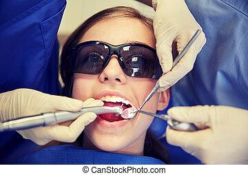 female dentists treating patient girl teeth
