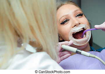 Female dentists treating patient in the clinic.