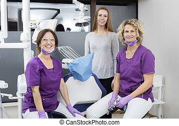 Female Dentists With Young Patient Smiling In Clinic