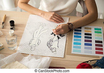 Female designer hands painting embroidery pattern scheme on fash