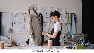 Female designer putting garment on mannequin working in...