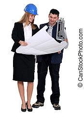 Female designer showing plans to tiler