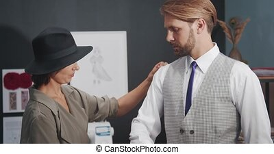 Professional dressmaker in trendy hat measuring handsome man at modern studio. Beautiful woman tailoring business suit for bearded client.