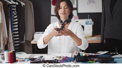 Attractive female designer in white shirt taking photos of sketches on modern smartphone. Dark-haired woman using digital gadget at workshop studio.