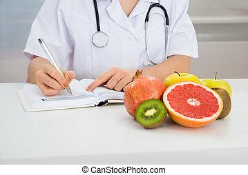 Female Dietician Writing Prescription - Close-up Of Female...