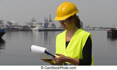 Female docker in an industrial harbor working her way through a checklist on her clipboard