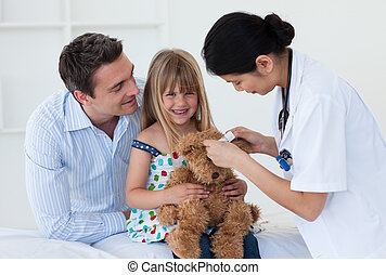 Female doctor and happy little girl examing a teddy bear in the hospital